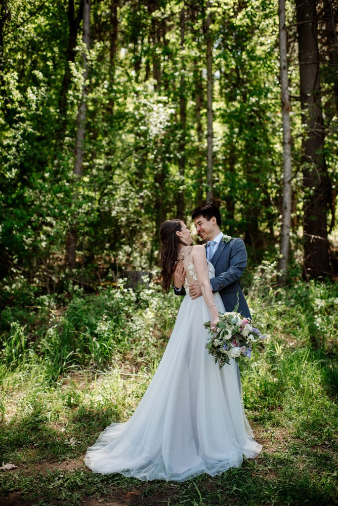 couple in woods with summer light wedding at round barn