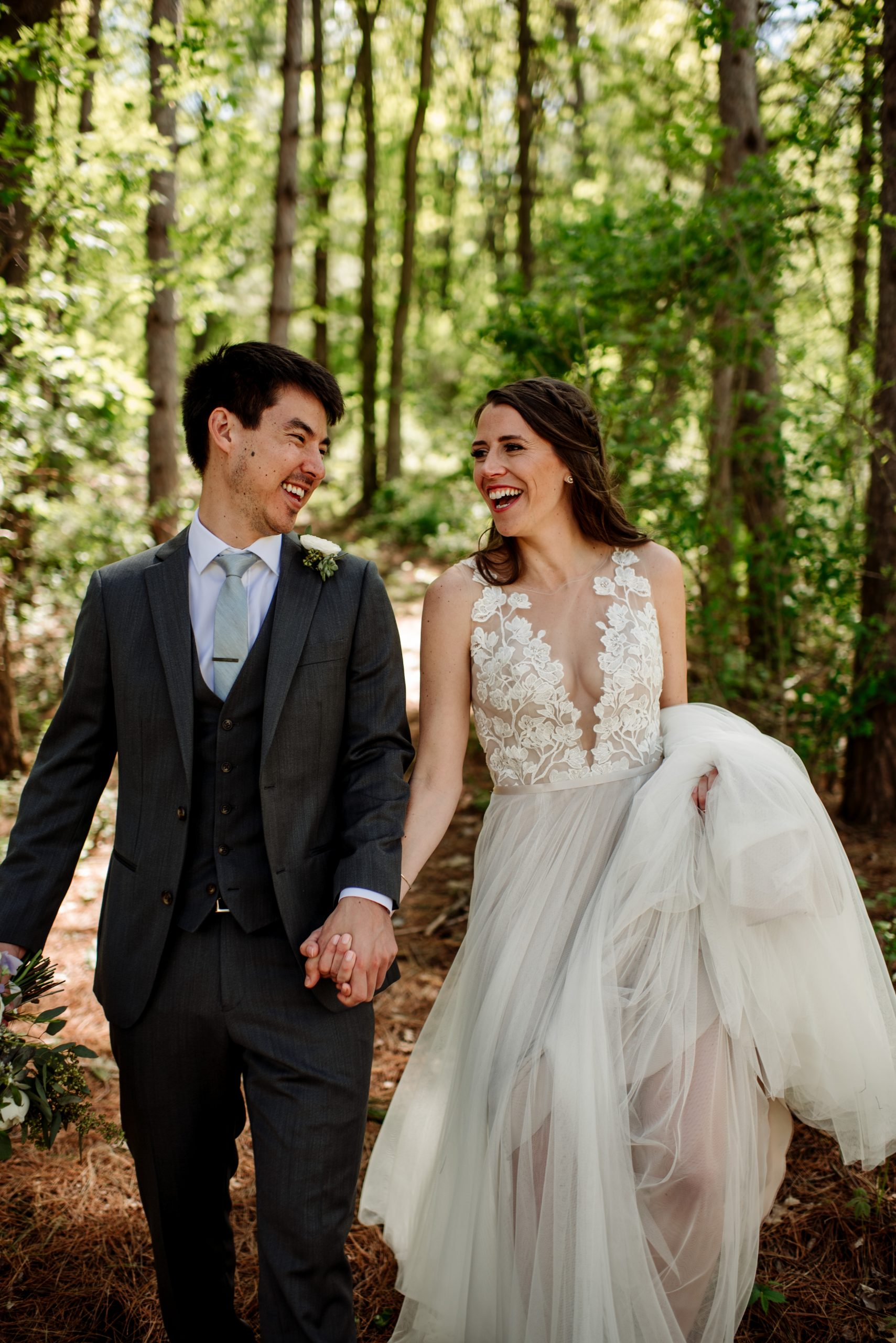 couple laughing and walking through the woods at wedding at round barn mn