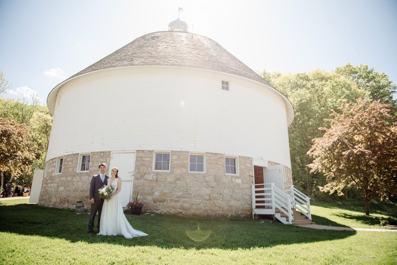 bride and groom in front of round barn wedding venue, mn