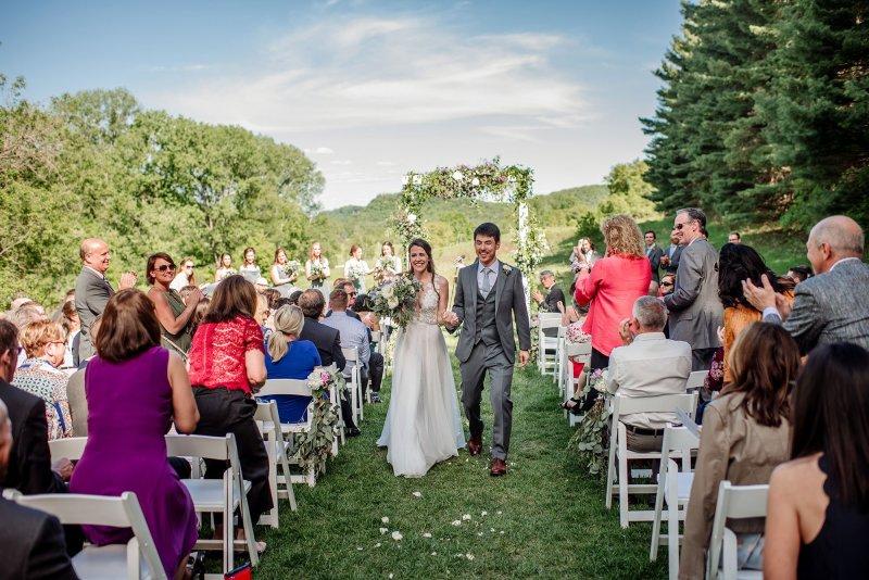bride and groom walk down aisle wedding at round barn