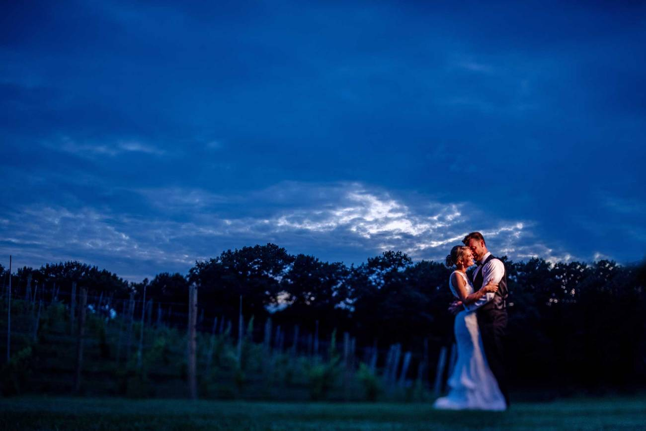 bride nad groom embrace with dramatic blue skies at night 7 vines vineyard wedding mn