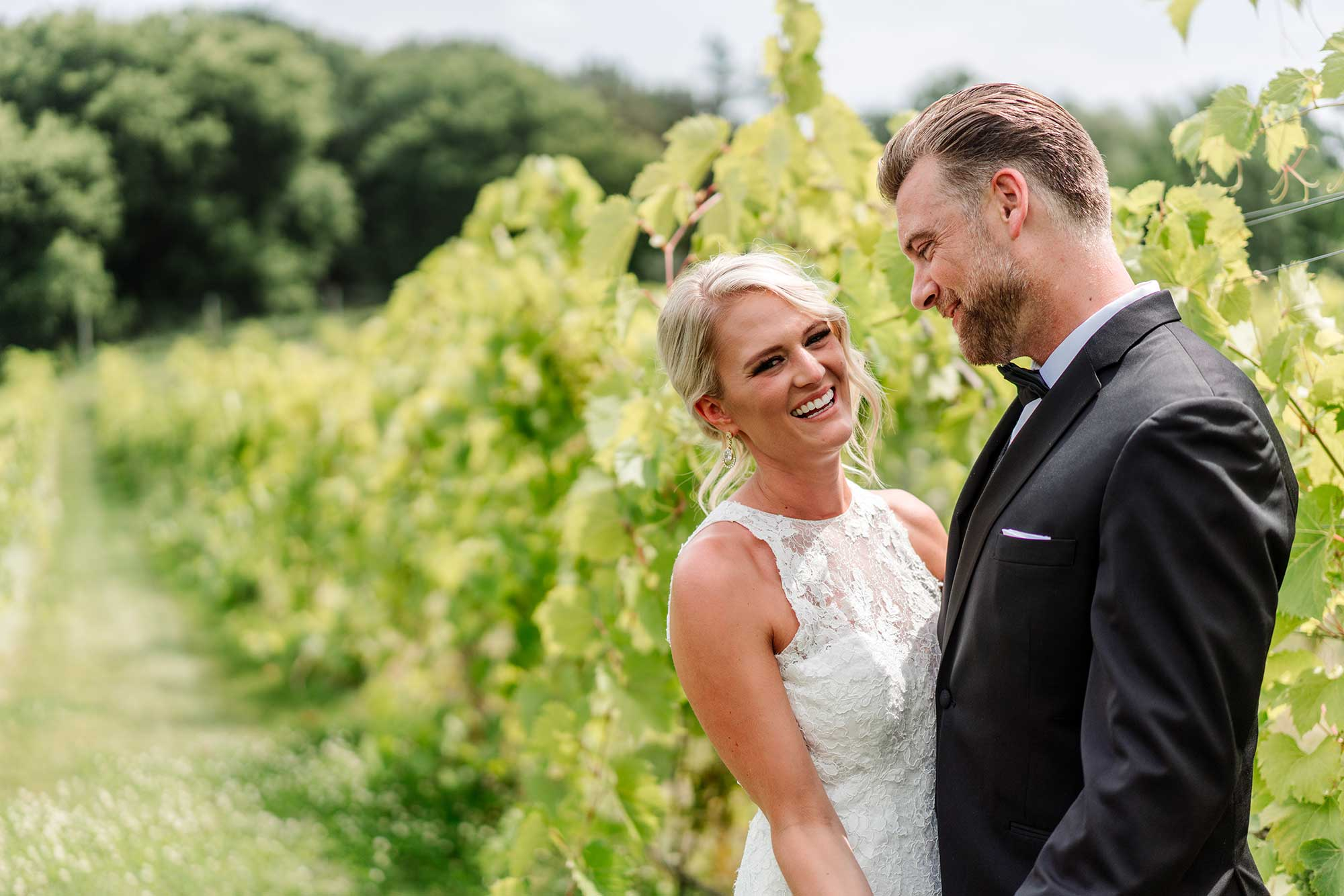 bride laughing in vineyard