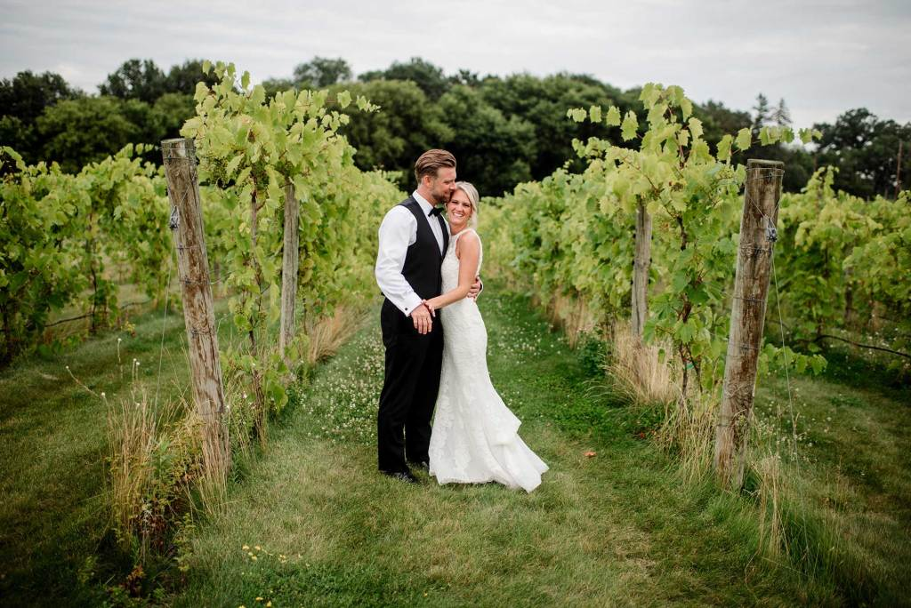 bride and groom easily stroll around vinyard in delano mn