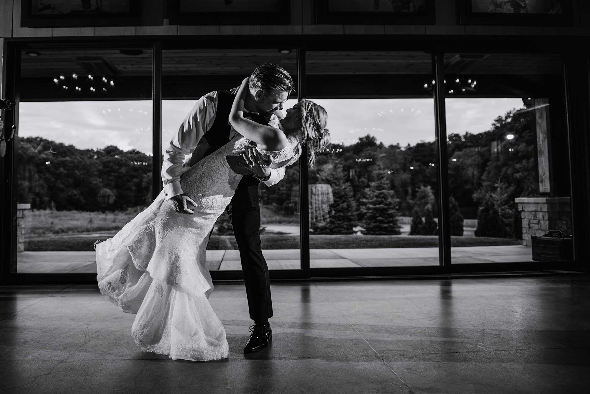 groom dips bride at end of first dance in front of panoramic windows of 7 vines vinyard wedding
