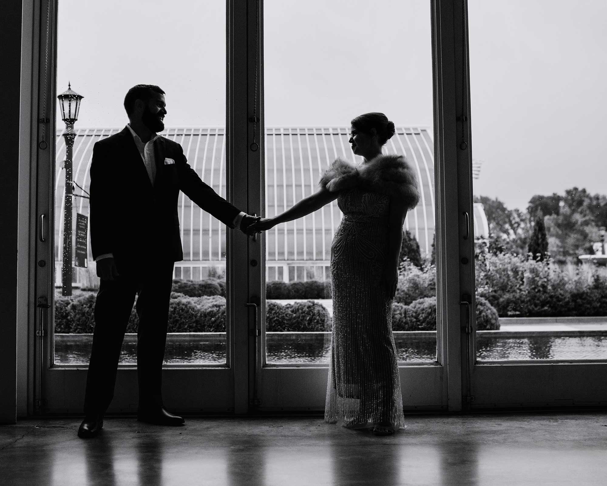 silhouette of bride and groom framed by tall windows of Como Conservatory st paul
