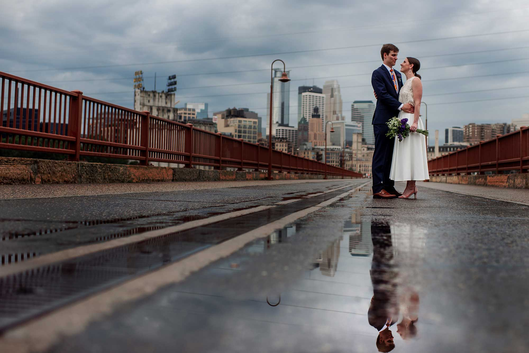 couple reflected in puddle on stone arch bridge in minneapolis