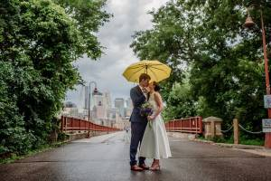 couple cuddle under yellow umbrella for minneapolis brewhouse small wedding