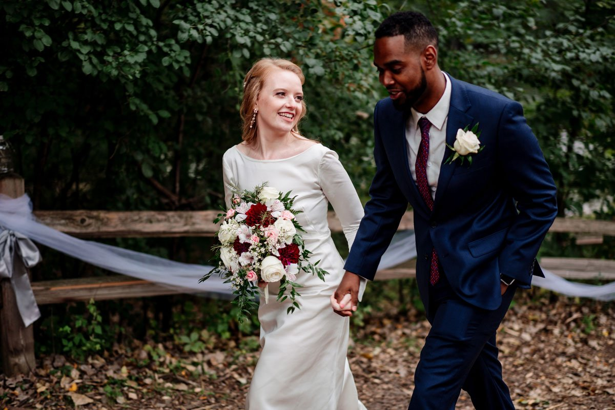 bride and groom walk in path after mn camp wedding