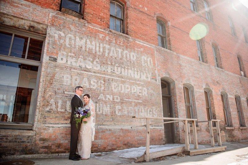 bride and groom by warehouse buildings in minneapolis
