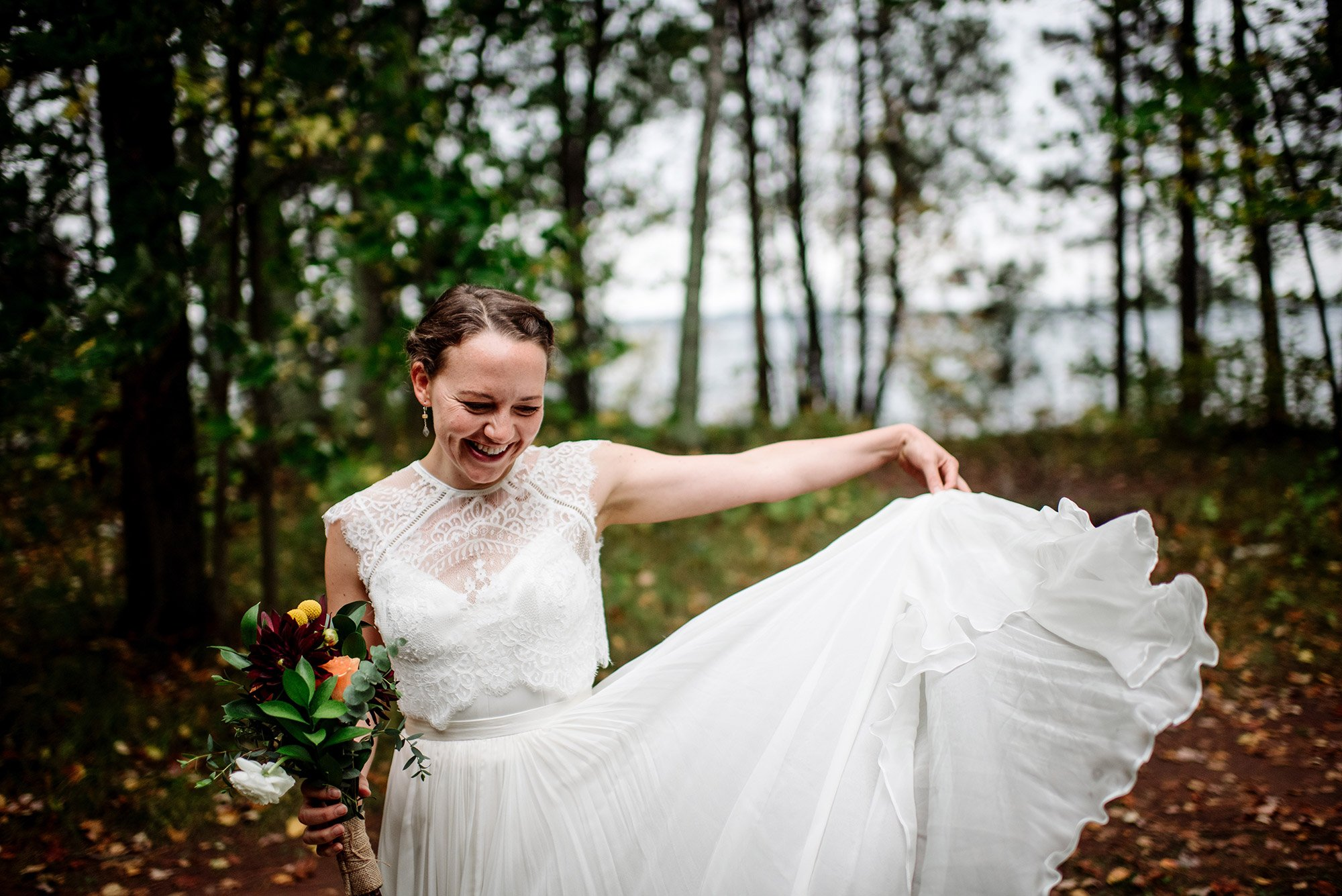 bride playing with lace dress MN wedding at Camp Miller