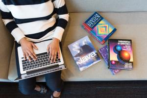 Woman working on laptop with coding books beside her