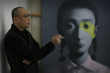 Zhang Xiaogang with one of his Family Portrait series paintings. Photo: GettyAFP.