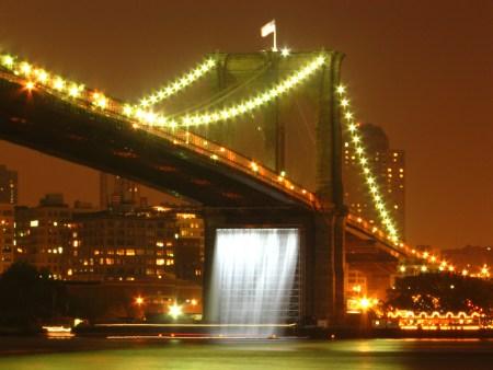 One of Olafur Eliasson's New York City Waterfalls, under the Brooklyn Bridge, seen at night.