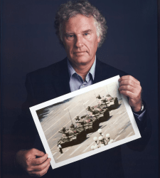 """An undated photograph of Jeff Widener with a print of """"Tank Man."""""""