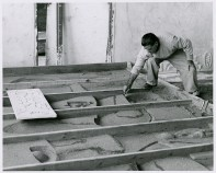 Nivola sculpting the sand in the forms referencing a small model, circa 1960