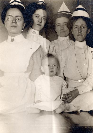 Group portrait of four nurses and an infant patient, circa 1910
