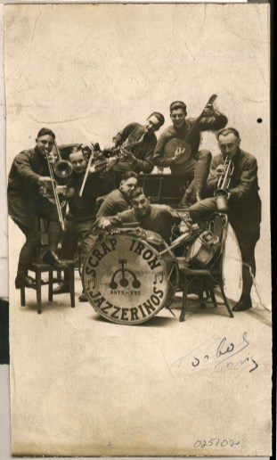 "St. Lousians Arshav Nushan, drums, Edwin Dakin, violin, Syl Horn, banjo, and Clarence Koch, trumpet; Clevelanders Russell Hauslaib, saxophone, Clayton Thirkill, piano, and Albert Angelotta, trombone, made up the ""Scrap Iron Jazzerinos"", circa 1919"