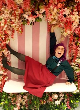 Becki is sitting on a white bench surrounded by beautiful pink and white flowers with a pink and white vertical striped background. They are leaning back on one arm, with both their legs outstretched in the air, and their other arm reaching up to touch the flowers. Their mouth is wide open in a truly joyful laugh, as they look off camera, incredibly happy with their ridiculous pose. They have dark but powerful purple hair, and are wearing a pink A-line skirt, green tights, a green long sleeved shirt, a turquoise quirky bow-tie, and black braces with a variety of pin badges on them. They have no shoes on, and look completely happy and carefree.
