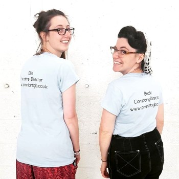 Ellie and Becki are standing in front of a white wall, with their backs to the camera to show off the back of their t-shirts, which have their names, title - Ellie is Theatre Director, and Becki is Company Director, and the OmniArts web address on them - www.omniartsgb.co.uk. They are twisting their heads round to look at the camera, and are both beaming. Ellie has long brown hair in a ponytail, and black rimmed glasses. Becki has dark brown hair in a 1940s vintage style with a white snood and horn-rimmed glasses.