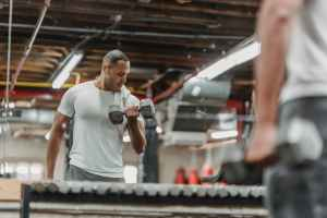 reflection in miror of man with dumbbells