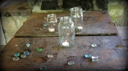 Three votive candles in jars....