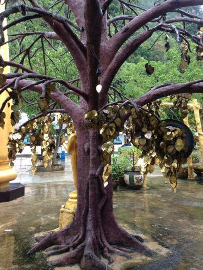 a tree with metal leaves that had the imprint of Buddha