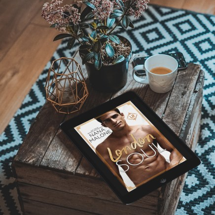 London Soul promo photo--ereader on rustic chest still-life style with hot drink, candle, and plant on geometric rug