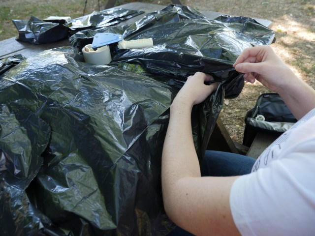 Image of end of trash bag being tucked into another trash bag in preparation for taping
