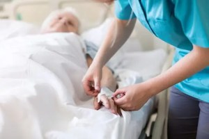 caregiver starting an IV in her mother's hand