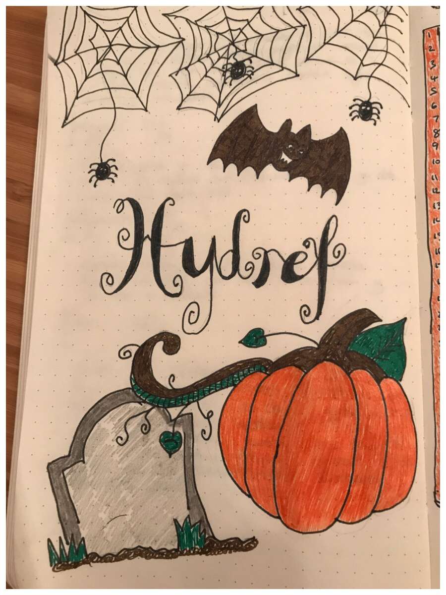 "Drawing of pumpkin, gravestone, bat and spiderwebs with the word ""Hydref"" (October in Welsh) in calligraphy. My hello October page in the bullet journal."