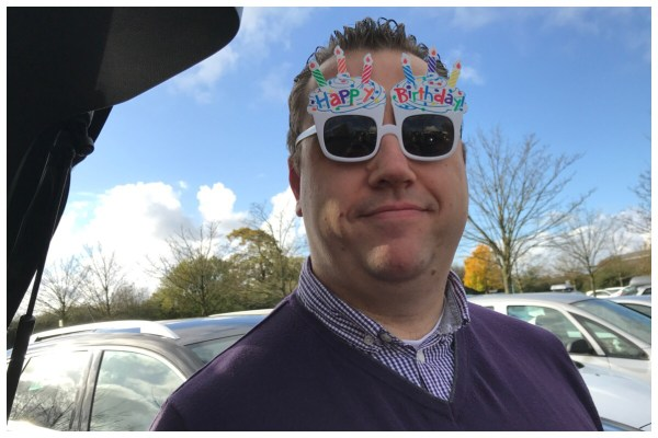 A photo of my husband wearing fun birthday glasses in front of a very blue sky