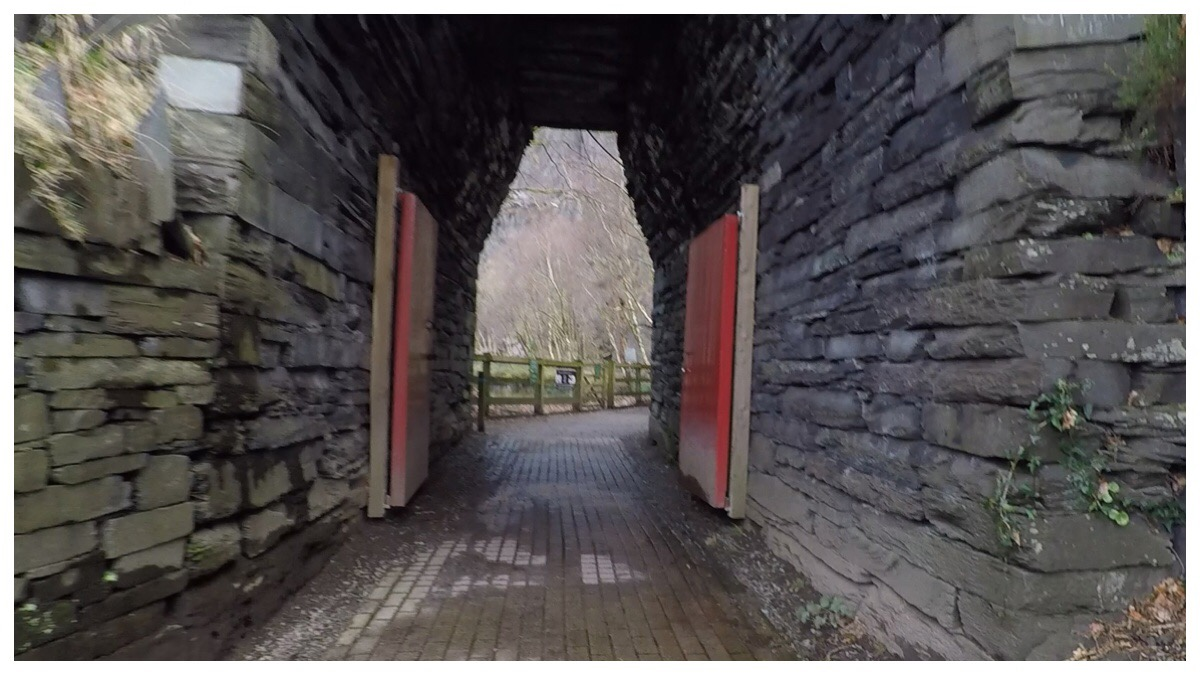 The entrance to Vivian Quarry - a red gate via a slate structure