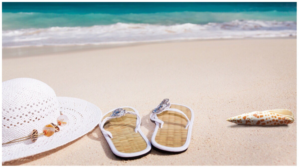 White hat, flip flops and shell on a sandy beach with waves crashing ashore in the background