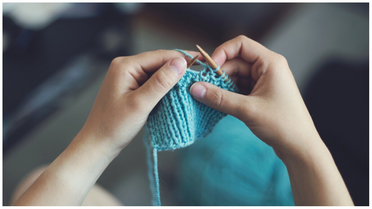 Pair of hands in the middle of knitting a blue piece of knitwear