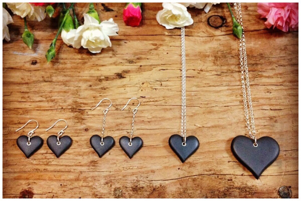 Beautiful heart shaped slate necklaces and earrings (handcrafted by Mari Eluned) against a wooden backdrop.