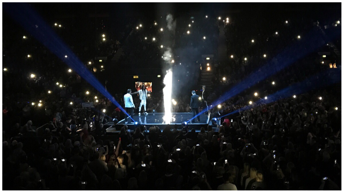 A photo of Boyzone in the middle surrounded by darkness except for a smattering of phone lights. In the middle is a bright light which signifies Steo's energy during a performance of I Can Dream