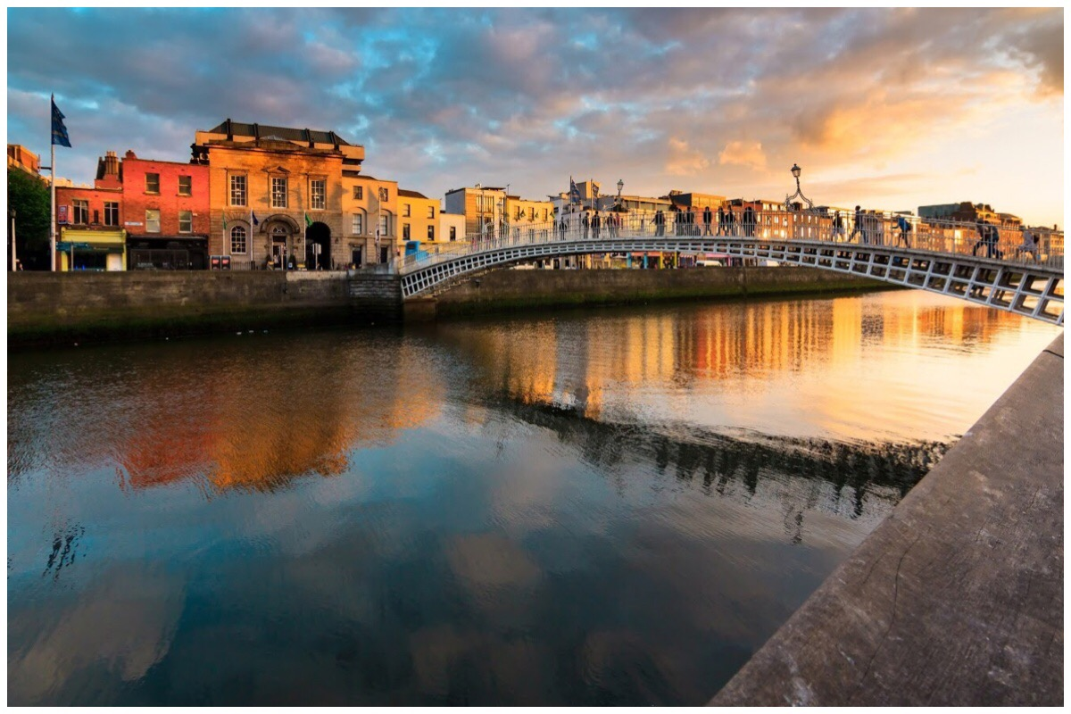 The Ha'penny Bridge over the River Liffey in Dublin with sunset in the background.