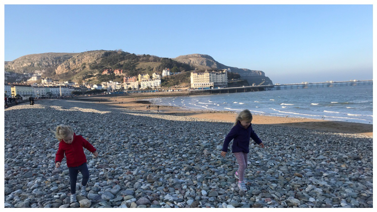 The girls looking for seaglass at Llandudno North Shore with the Grand Hotel in the background