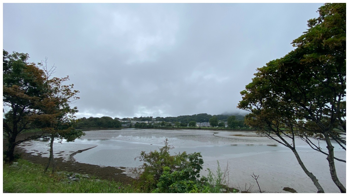 Cob Crwn Porthmadog with the lake in foreground and grey sky in the background