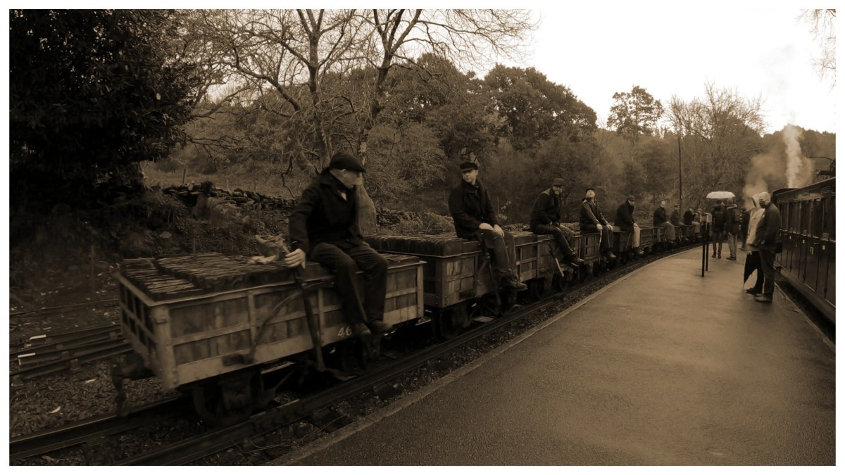 Sepia tone photo of people sat on slate laden wagons