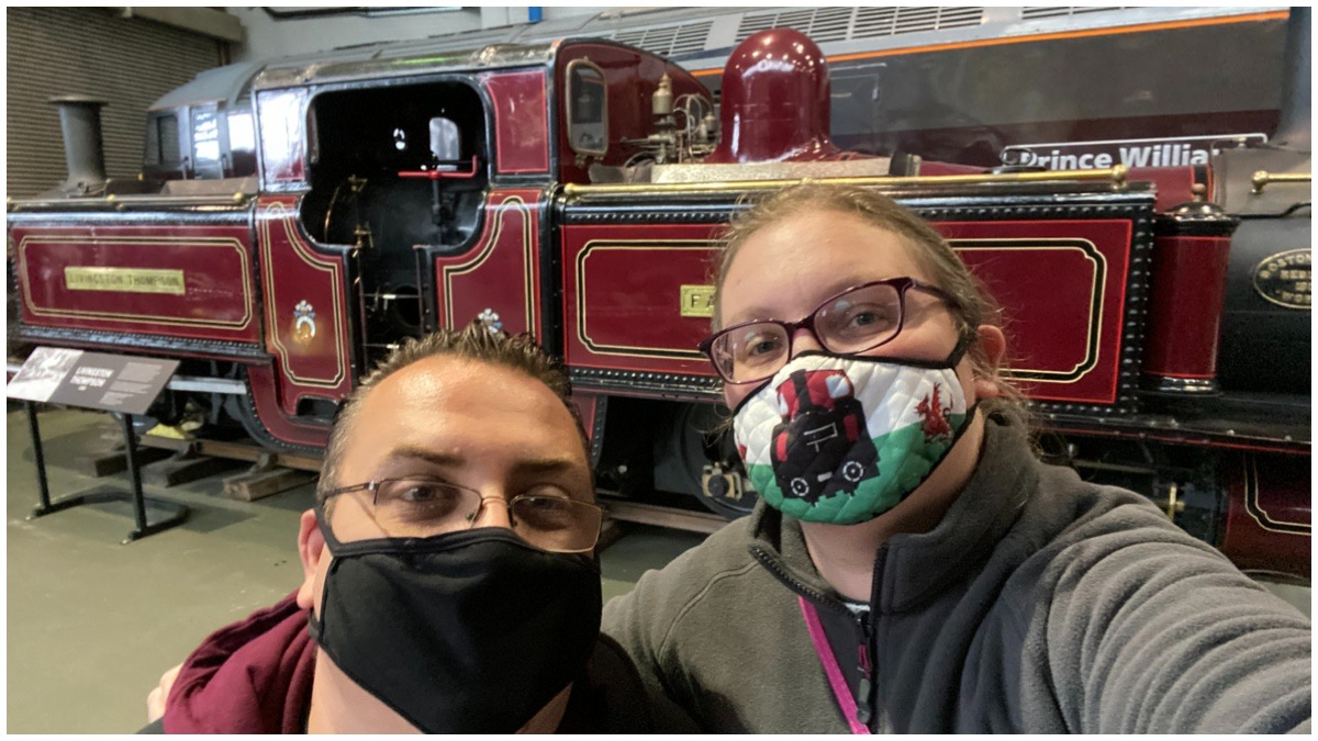 Husband and I wearing masks stood in front of Livingston Thompson at the National Railway Museum
