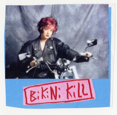 Kathleen Hanna manhandling a motorcycle on a photo shoot (Courtesy of Kathleen Hanna, Bikini Kill, and the Fales Library & Special Collections, New York University)