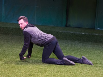 An actor walking on his hands and knees on a grass-covered stage. He is pretending to be a dog.