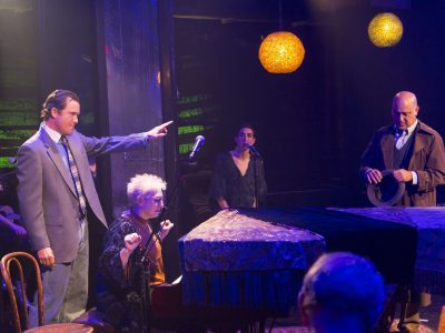 Actors in a scene: A man pointing in a dark nightclub with others around and a grand piano and player in front of him