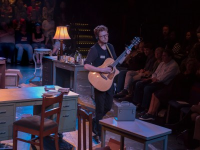 An actor dressed as a house manager plays the guitar on a stage that is full of desks and cabinets. The audience sits behind him.