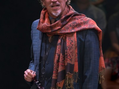 A bearded man in a scarf speaking onstage, the audience sits behind him