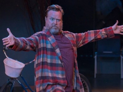 An actor in a scene: A bearded man with arms outstretched