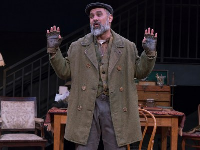 Rajesh Bose on stage with his hands raised in shabby clothes as Alfred P. Doolittle in Bedlam's Pygmalion