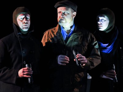 Three actors on a dark stage with flashlights shining in their faces