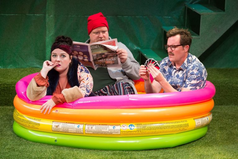 Three adult actors sitting in a rainbow colored inflatable baby pool, one biting her nails, one reading a newspaper, one playing cards